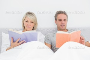 Relaxed couple reading in bed at home in bedroom